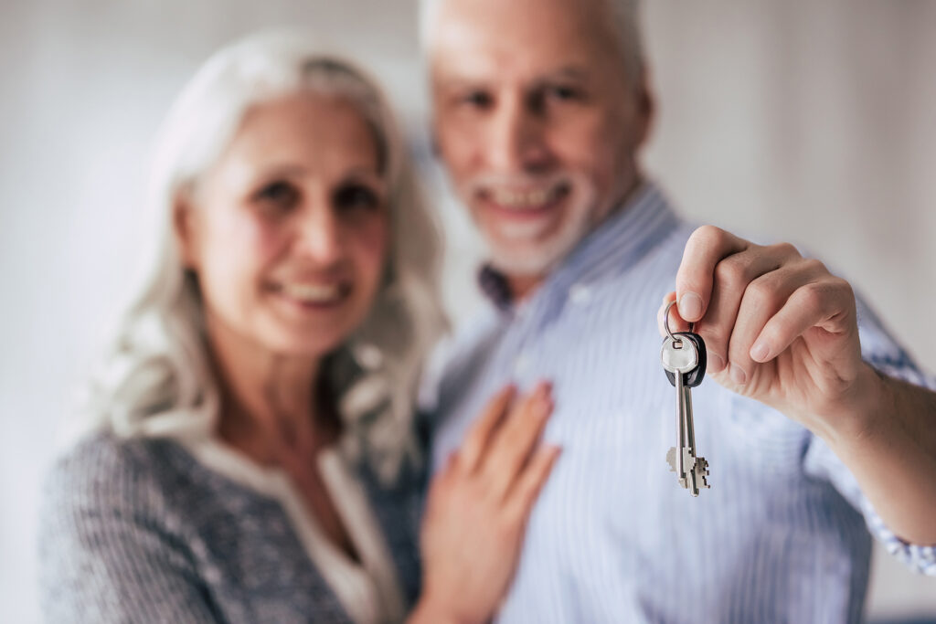 Love lives forever! Senior couple at home. Handsome old man and attractive old woman are spending time together while standing with keys in hands. Moving day; Shutterstock ID 1050674651; Purchase Order: booj Website Launch; Job: ; Client/Licensee: ; Other: